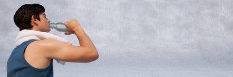 Тренировка и питьевая вода человека против серой стены Стоковая Фотография