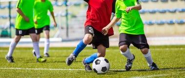Тренировка и футбольный матч между командами молодости Молодые мальчики играя футбол Стоковое фото RF