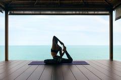 Тренировка йоги Женщина в спорте одевает протягивать тело около моря стоковая фотография