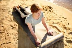 Тренировка йоги зрелой женщины практикуя на открытом воздухе на пляже около реки стоковые изображения rf