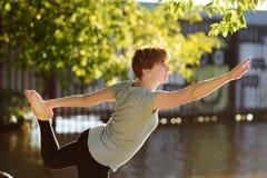 Тренировка йоги зрелой женщины практикуя на открытом воздухе на пляже около реки стоковое фото