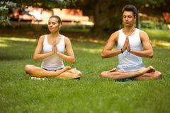 Тренировка йоги Молодые пары размышляя в парке лета Стоковое Изображение RF