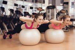 Тренировка матери и дочери с шариками пригонки на спортзале Они смотрят счастливыми, модными и подходящими стоковые изображения rf