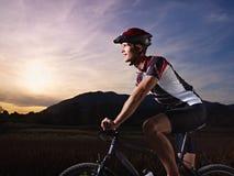 Тренировка молодого человека на bike горы на заходе солнца Стоковое Изображение RF
