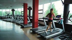 Тренировка молодой женщины на третбане в фитнес-клубе акции видеоматериалы