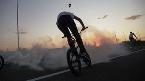 Тренировка молодых велосипедистов ехать и практикуя циркаческие методы на задействуя цепи внешней на заходе солнца с дымом - сток-видео