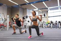 Тренировка молодого человека и женщины с штангой в спортзале Стоковое фото RF