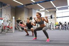 Тренировка молодого человека и женщины с штангой в спортзале Стоковое Изображение
