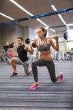 Тренировка молодого человека и женщины с штангой в спортзале Стоковые Фотографии RF