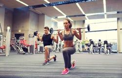 Тренировка молодого человека и женщины с штангой в спортзале Стоковая Фотография RF