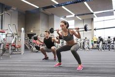 Тренировка молодого человека и женщины с штангой в спортзале Стоковое Фото