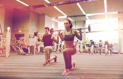 Тренировка молодого человека и женщины с штангой в спортзале Стоковое Изображение RF