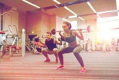 Тренировка молодого человека и женщины с штангой в спортзале Стоковые Изображения RF