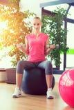 Тренировка молодой женщины в спортзале с гантелями перед зеркалом сидя на fitball Стоковая Фотография RF