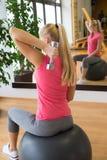 Тренировка молодой женщины в спортзале с гантелями перед зеркалом Стоковые Фото