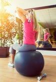 Тренировка молодой женщины в спортзале с гантелями перед зеркалом Стоковое Фото
