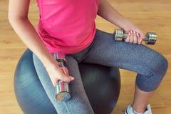 Тренировка молодой женщины в спортзале с гантелями, усаживании на fitball Стоковые Изображения