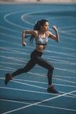 Тренировка на идущем стадионе следа, концепция спортсменки маленькой девочки идущая Стоковое фото RF