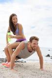 Тренировка пар фитнеса делая смешной нажим-вверх стоковая фотография