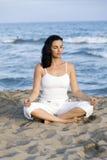 тренировка пляжа делая йогу женщины стоковое изображение