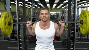 Тренировка прочности в спортзале парень в футболке делая сидения на корточках с штангой культурист делая тренировку с штангой Стоковые Изображения RF