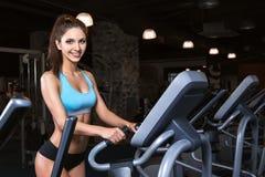Тренировка разминки девушки красоты на эллиптическом велосипеде Стоковые Фото