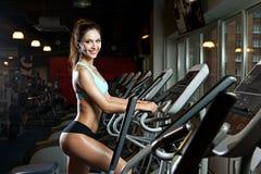 Тренировка разминки девушки красоты на эллиптическом велосипеде Стоковые Изображения
