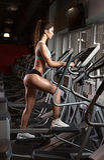 Тренировка разминки девушки красоты на эллиптическом велосипеде Стоковое фото RF