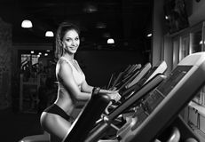 Тренировка разминки девушки красоты на эллиптическом велосипеде Стоковые Изображения RF
