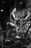 Тренировка разминки девушки красоты на эллиптическом велосипеде Стоковые Фотографии RF