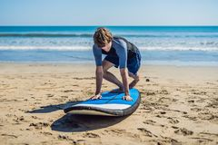 Тренировка серфера молодого человека перед идет к компановке на пляже песка L стоковая фотография