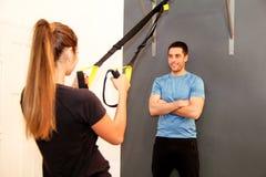 Тренировка спортсменки с диапазоном сопротивления trx с тренером Стоковые Изображения