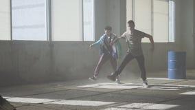 Тренировка умелых тазобедренных hopers 2 танцора человека успешных танцуют breakdance в получившемся отказ пылевоздушном здании сток-видео