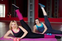 Тренировка 2 усмехаясь девушек на циновках в фитнес-центре Стоковая Фотография