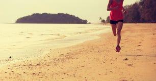Тренировка утра женщины бежать на пляже стоковое фото