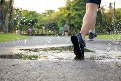 Тренировка человека бежать через лужицу брызгая его ботинки стоковые фотографии rf
