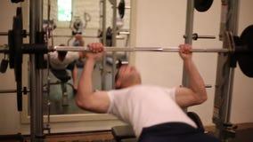 Тренировка человека в спортзале Мужчина подготавливая и делая жим лёжа с баром сток-видео