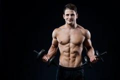 Тренировка человека красивой силы атлетическая нагнетая вверх muscles с гантелями в спортзале Тело фитнеса мышечное на черноте стоковые фотографии rf