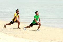 Тренировка 2 человек на пляже стоковая фотография