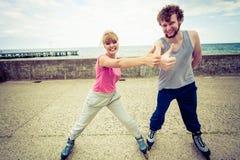 Тренировка 2 людей на rollerblades езды взморья Стоковое Фото