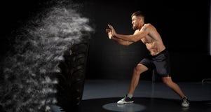 Тренировка Crossfit - человек слегка ударяя автошину Стоковые Изображения