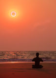 Тренировки йоги на заходе солнца океана. Силуэт человека. Стоковые Фотографии RF