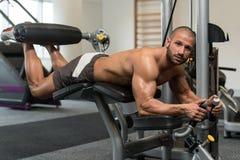 Тренировки скручиваемостей ноги оздоровительного клуба лежа Стоковые Изображения RF