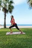 Тренировки спорта разминки женщины сидят на корточках outdoors на пляже Стоковое Изображение