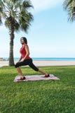 Тренировки спорта разминки женщины сидят на корточках outdoors на пляже Стоковые Фотографии RF