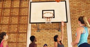Тренируйте команду средней школы порции для того чтобы вести счет цель пока играющ баскетбол акции видеоматериалы