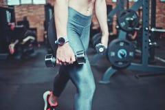 Тренируя концепция Крупный план напряженных мышц ноги в гетры Женщина фитнеса с телом спорт работая с гантелями в спортзале стоковые фото