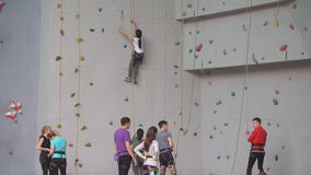 Тренируя молодые спортсмены на взбираясь стене Группа в составе альпинисты практикуя на крытом спортзале утеса видеоматериал
