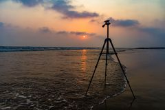 Тренога в предпосылке пляжа восхода солнца на море для фотографии пляжа тренога в предпосылке пляжа восхода солнца на море для ph Стоковые Фотографии RF