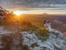 Тренога hiker женщины установленная с камерой на, который подвергли действию скалистом саммите стоковые фотографии rf